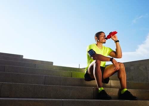 Atleta che beve seduto sulle scale.