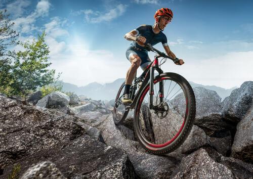 Uomo che affronta le difficoltà del ciclismo di montagna.