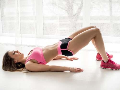 Donna che allena fianchi e glutei con il ponte per aumentare la flessibilità.