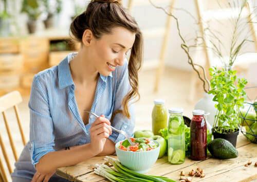 Donna felice che mangia un'insalata per migliorare il benessere.