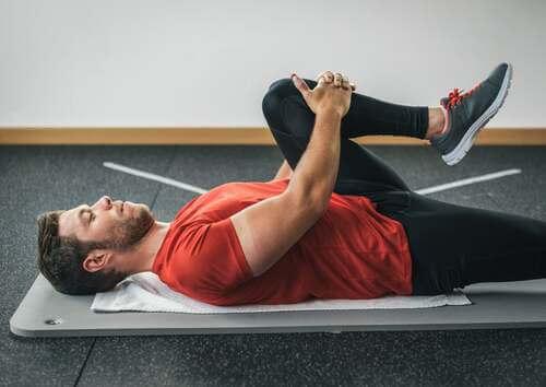 Uomo che fa stretching per allungare il gluteo portando il ginocchio al petto.