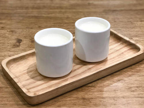 Tazze di latte tiepido su un vassoio.