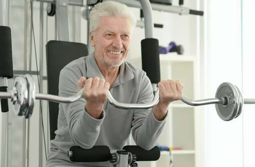 Uomo anziano in palestra che fa sollevamento pesi.