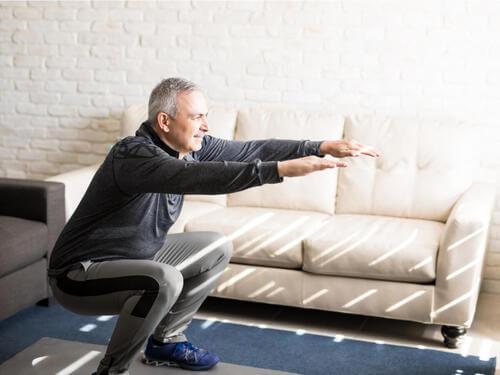 Uomo anziano che fa squat.