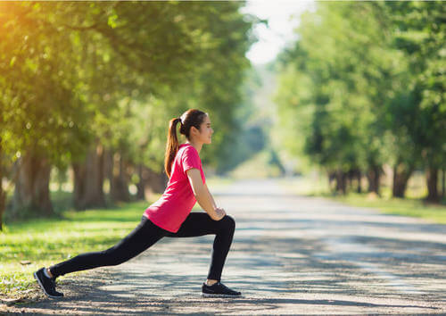 Donna fa stretching alle gambe nel parco.