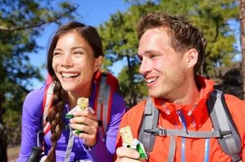 Coppia di atleti in montagna mangia delle barrette proteiche.