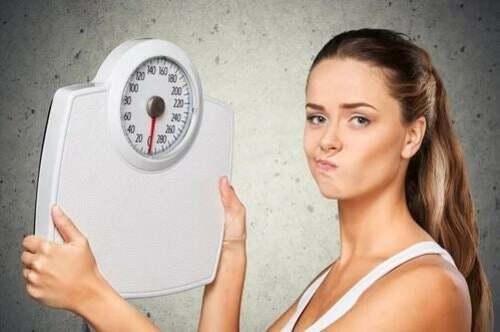 Donna con in mano una bilancia dopo aver fatto esercizio per perdere peso.