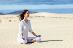 Donna che fa yoga sulla spiaggia.
