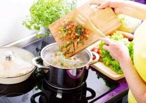Donna che prepara una minestra.
