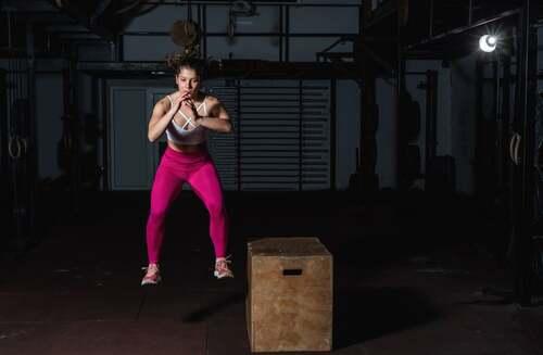 Ragazza che esegue un salto laterale con il box di CrossFit.