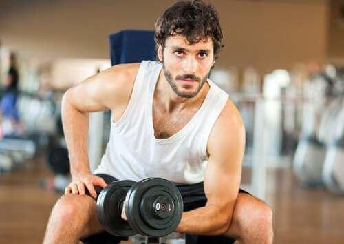 Uomo che fa esercizio fisico in palestra per combattere il metabolismo lento.