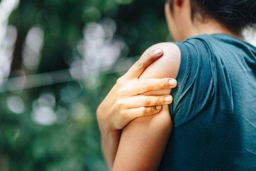 腱損傷の原因は何ですか? 肩が痛い女性