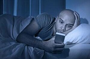 ベッドで携帯を見る男性 眠れないのはなぜ?