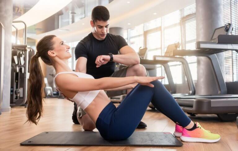 Dame som gjør mageøvelser med en trener tilstede.