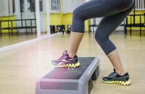Kvinne trener lårene med en stepper.