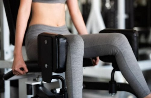 Dame som trener benene i en maskin.
