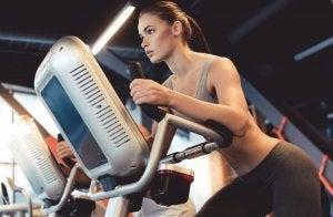En dame trener med elipsemaskin.