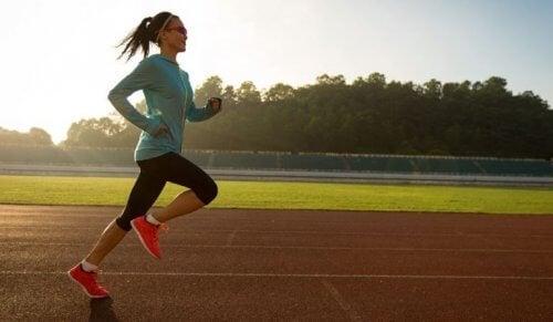 Kvinne jogger rundt idrettsbane.