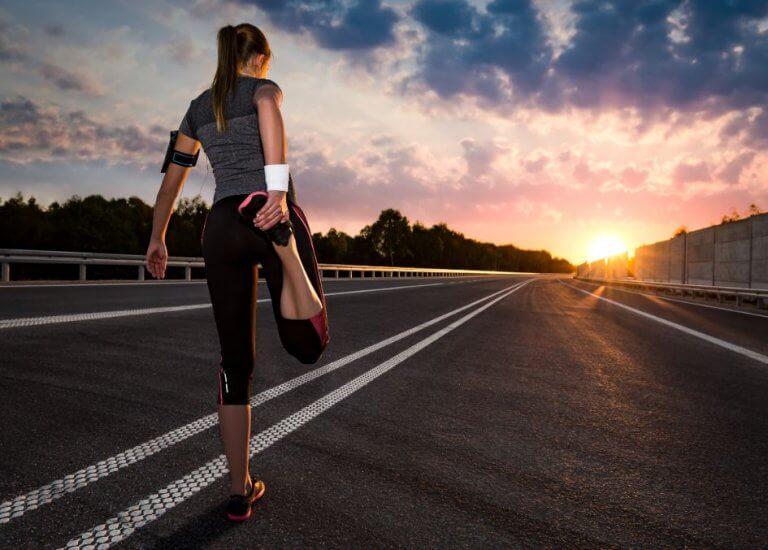 En jente som strekker ut før hun skal løpe.