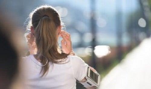 Jente som løper med hodetelefoner.