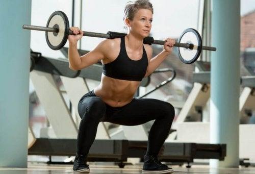 Kvinne som gjør knebøy med vektstang for å utvikle setemusklene.