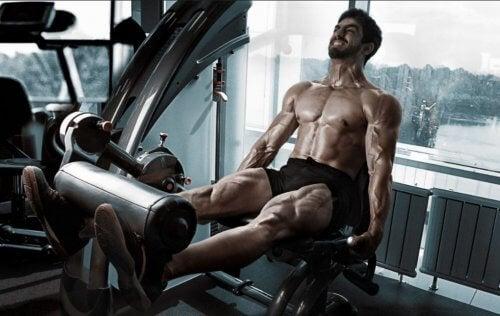 En mann som trener beina i en maskin. Bruker en øvre/nedre delt treningsrutine.