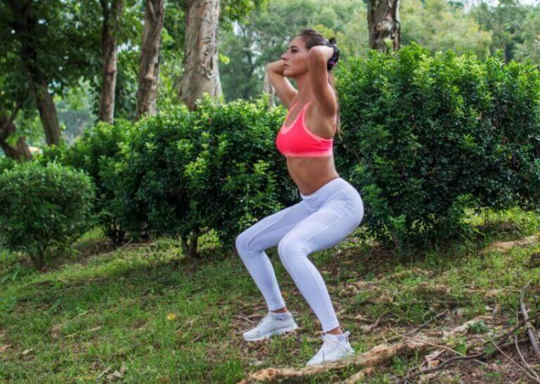 Dame som trener knebøy i parken.