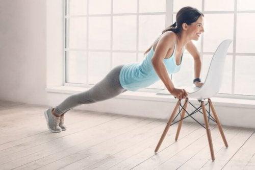 Kvinne utfører øvelser med stol.