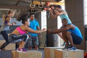 Kvinne og mann trener beina ved å hoppe opp på en kasse.