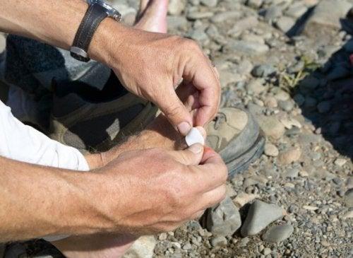Mann setter plaster på foten