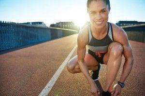 Kvinne knyter sko og smiler mot kamera.