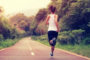 Kvinne løper omringet av vegetasjon