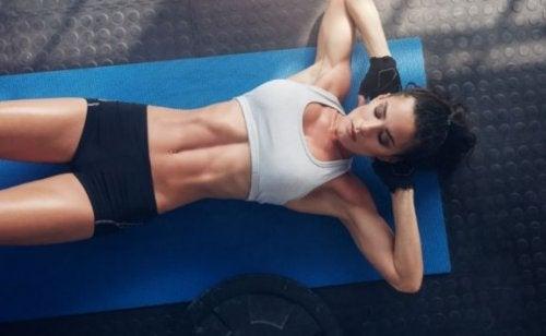Kvinne som gjør sit-ups, som er en grunnleggende øvelse for å forme kroppen vår.