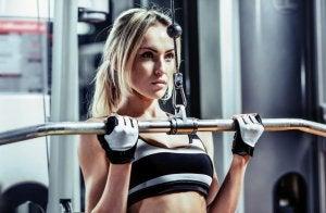 Kvinne trener styrke på treningsstudio.