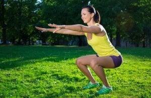Kvinne utfører enkle knebøy i en park.