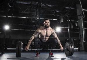 Mann trener med vekter for å øke muskelmassen.