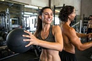 Mann og kvinne trener med medisinball på treningssenter.
