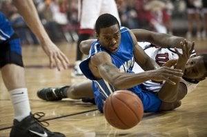 Basketballspiller har blitt taklet og befinner seg på gulvet.