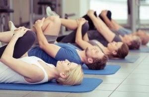 En gruppe mennesker utfører yogastillingen apanasana.