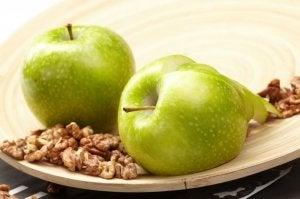 Fat med to grønne epler og valnøtter.