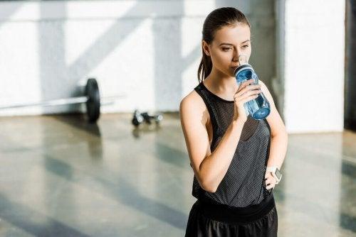 Kvinne drikker vann i treningssal.