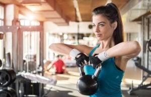 Kvinne løfter kettlebell på treningsstudio.