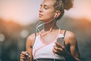 Kvinne lytter til musikk mens hun trener utendørs.