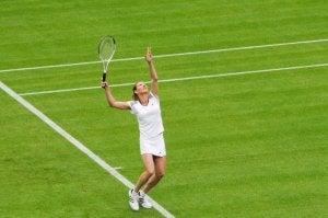 Kvinne spiller tennis på gressmatte.