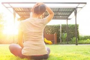 Kvinne tøyer nakken sittende utendørs på gress.