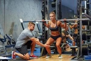Trener viser kvinne hvordan hun bør trene knebøy med vektstang bak hodet.