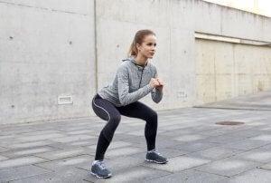 Kvinne trener knebøy utendørs.