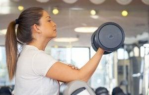 Kvinne trener bicepscurl med manual på treningsstudio.