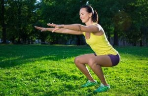 Kvinne utfører air squats i en park.