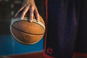 Nærbilde av en spiller som holder en basketball.
